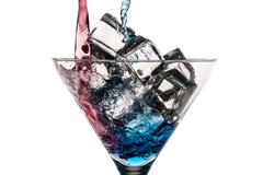 Blue and red liqueur poured into a glass with ice cubes on white background Stock Photos