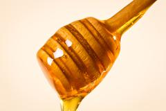 Honey dipper with honey on white background Stock Photos