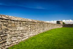 medieval wall surrounding the castle with stone - stock photo