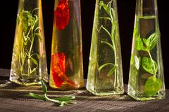 four bottles with vegetable oil and fresh spices - stock photo