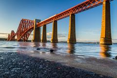 train riding on the forth road bridge at sunset - stock photo