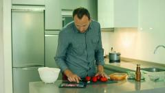 Man cooking in the kitchen and looking on the recipe in the internet Stock Footage