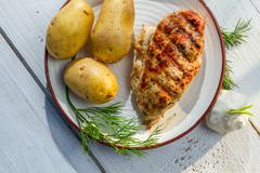 Roasted chicken breast with potatoes and dill on plate Stock Photos