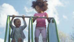 Two young children playing on a slide in slow motion Stock Footage