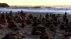 Stacked rocks at the beach at sunset Stock Footage