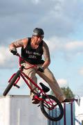 Man spins his bike in midair performing at bmx show Stock Photos