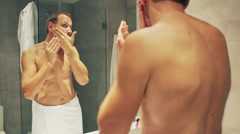 Man spreads cream on his face in the bathroom after shower Stock Footage