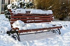 Snow-covered bench warms in the sun - stock photo