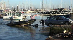 Stock Video Footage of young men attach rib boat to trailer at lymington, england