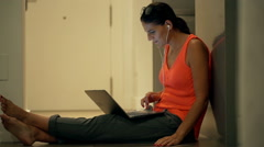 Woman with earphones sitting on the floor and working on laptop - stock footage