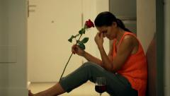 Heartbroken woman sitting on the floor with red rose and drinking wine Stock Footage