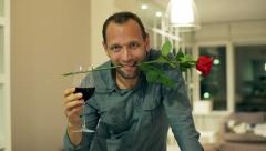 Happy man with rose and wine flirting to the camera Stock Footage