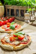 closeup of fresh ingredients for a mini pizza with mushrooms - stock photo