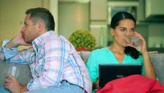 Couple sitting on the sofa after quarrel and doing faces, steadycam shot Stock Footage