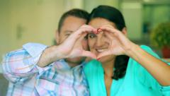 Happy couple making heart to the camera and smiling, steadycam shot Stock Footage