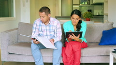 Man browsing album and woman using tablet on the sofa - stock footage