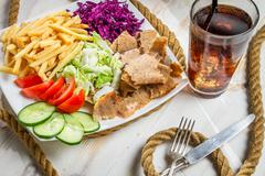 closeup of vegetables, fries and meat kebab served with cold coke - stock photo
