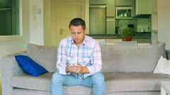 Man sitting on the sofa and tweeting on the smartphone - stock footage