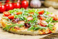 closeup of pizza with parma ham - stock photo