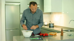 Man preparing salad using recipe on the internet and cutting tomato Stock Footage