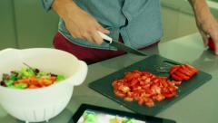Man chipping tomato on the board and looking on the recipe on tablet Stock Footage
