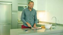Man cutting chicken in the kitchen and smiling to the camera Stock Footage