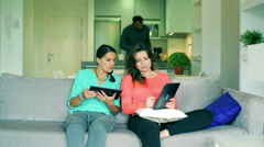 Female friends using tablets and man bringing them drinks Stock Footage