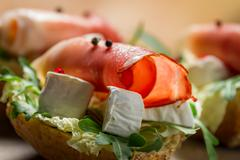 closeup of sandwiches made of parma ham and brie cheese - stock photo