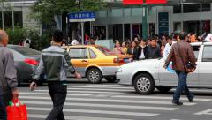 People cross the street during rush hour in Shanghai, China Stock Footage