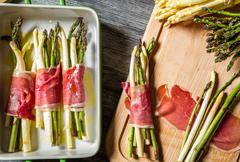 preparation baked asparagus with prosciutto - stock photo