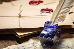 Close-up of inkwell with blue ink on the background of vintage letters Stock Photos