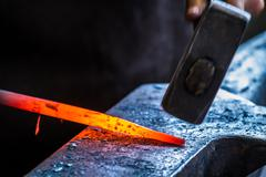 Blacksmith at work in anvil Stock Photos