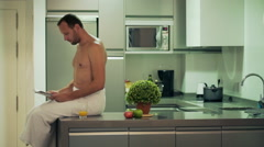 Man in the towel sitting on the countertop and reading newspaper Stock Footage