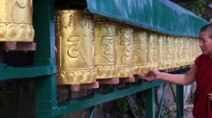 Tibetan Buddhist monk turning the prayer wheels at temple in Dharamsala , India Stock Footage