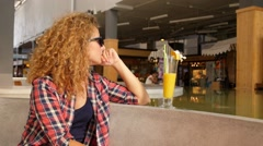 Beautiful Young Woman with Fruit Smoothie in a Cafe. Stock Footage