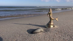 Antique brass bell with mermaid figure on sea beach Stock Footage