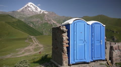Pair of modern toilets with Kazbek mountain in background Stock Footage