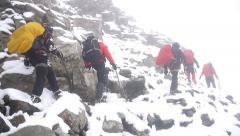 Big group of mountaineers walking through difficult terrain - stock footage