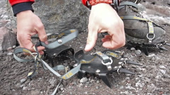 Alpine climber putting his crampons on shoes Stock Footage