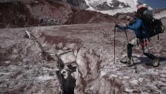 Group of Alpine Climbers jumping over big crevasse - stock footage