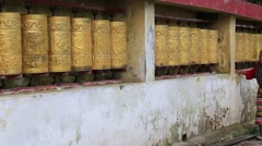 Old Tibetan woman turning the prayer wheels at temple in the Dharamsala , India Stock Footage