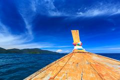 longtail boat on crystal clear sea at tropical beach - stock photo