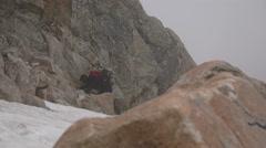 Alpinist climbing a rock next to snow field - stock footage