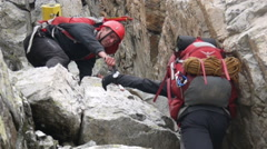 Alpine climbers helping each other with teamwork on the rock Stock Footage