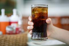 Hand holding glass of cola drink Stock Photos