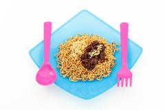 eating noodles with fork and spoon on white background - stock photo