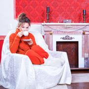 Woman with a cup of tea inside a red vintage room next to a christmas tree Stock Photos