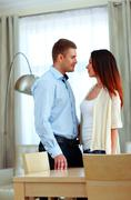 young beautiful couple standing at home and looking at each other - stock photo