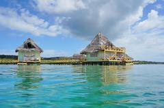 Tropical bungalows over water with thatch roof Stock Photos