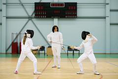 children fencers and their  trainer - stock photo
